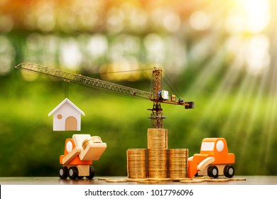 Stack coin with increase and tower crane and hoist brake and forklift truck and loader model with build a new house in public park, saving money and loan for construction real estate and home concept.