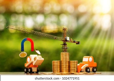 Stack coin with increase and tower crane and hoist brake with horseshoe magnet pull a money and forklift truck and loader model in public park, Success for Business construction real estate concept.