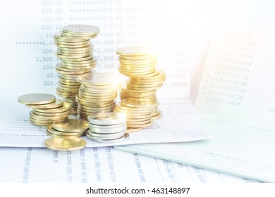 stack of coin on financial document and banking account in the background,color filter,lens flare