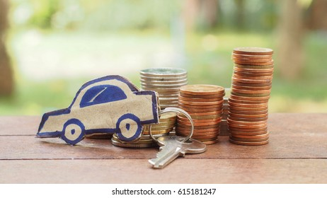 Stack of coin and paper car key on the wood table
