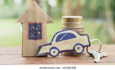 Stack of coin and paper house with car key on the wood table