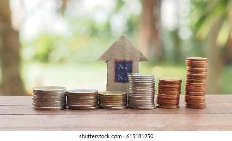 Stack of coin and paper house on the wood table