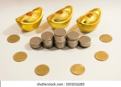 Stack of coins around blur golden coin and A sycee or yuanbao was a type of silver or gold ingot currency used in imperial China on white background
