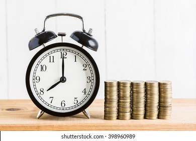 Stack of coins with black alarm clock , Time to Saving Concept