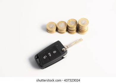 Stack of coins with black car key placed on isolated white background