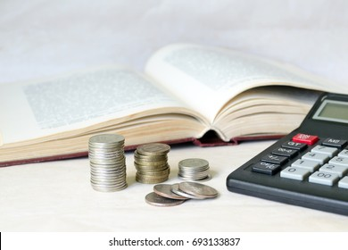 A stack of coins and a calculator in front of an open book. The concept of expensive education and low scholarship