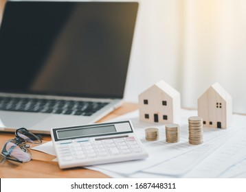 Stack of Coins with calculator,House model,tax form,glasses and tablet,Income Tax Raise Concept.