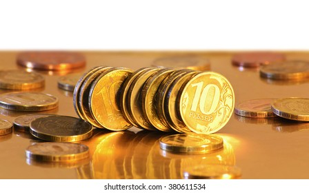 Stack of coins close-up on a gold background.