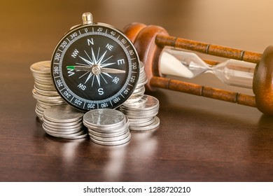 Stack of coins with compass and hourglass on wood table