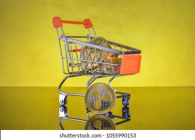 Stack of coins of crypto currency in mini shopping cart toy, concept of mining. Electronic virtual money for web banking and international network payment