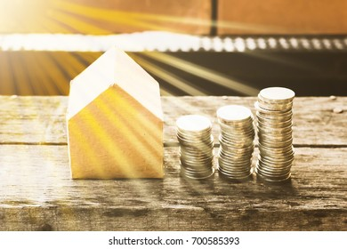 Stack of coins with miniature of small paper house isolated on wooden table background, dream light effect. House and money concept. Abstract conceptual image.