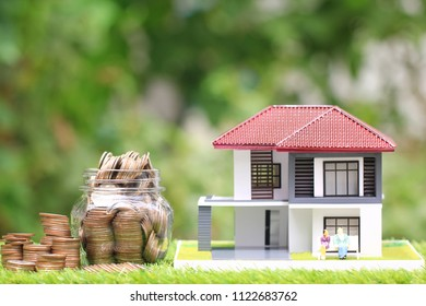 Stack of coins money in glass bottle with model house and miniature couple on natural green background, Save money for prepare in future and retirement concept