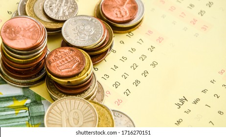 stack of coins on calendar, closeup shot, for finance background, coin calendar, Time is money, money calendar, Pay your bills against white calendar and coins background, euros background
