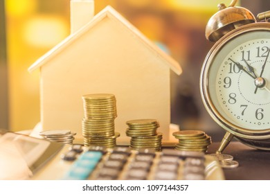 stack of coins planing to buy home with clock and house model , calculator over blur background