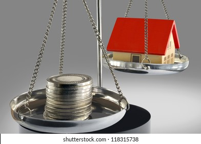 Stack of coins and a small house with a red roof on the scales