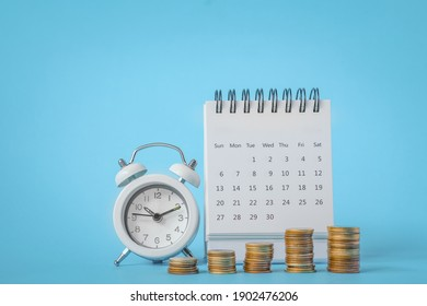 stack of coins , white analog clock and white calendar on grunge blue paper background for business and finance background