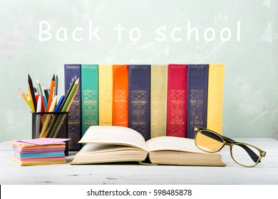 "A stack of color books, eyeglasses, stationery on a table and text ""Back to school"" on green background"