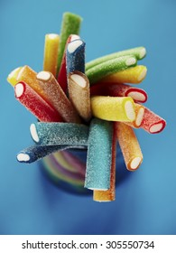 Stack of colored gummy sweet sticks on blue background