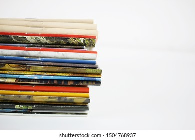 A stack of colored magazines on a white background, vertical end spine.
