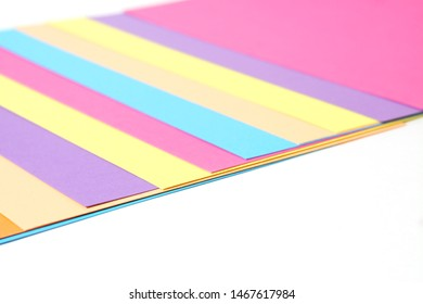 Stack of Colored Rainbow Paper (Yellow, Pink, Violet, Purple, Blue, Aqua, Green, Orange, Skyblue) Background. Close up.