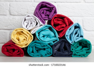 Stack of colored rolled clothes on a light wooden table. Close-up