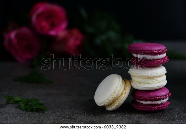 Stack of colorful assorted french macaroons on a dark stone background. Holiday concept. Low key