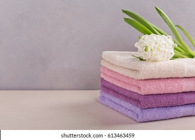 Stack of colorful bath towels with hyacinth flower on light background. Pastel colors cotton towels. Hygiene, fabric,spa and textile concept