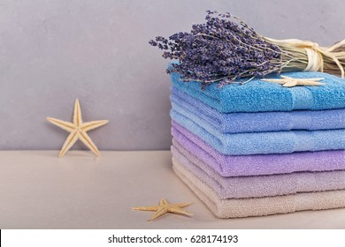 Stack of colorful bath towels on light background. Pastel colors cotton towels. Hygiene, fabric,spa and textile concept