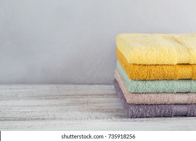 Stack of colorful bath towels on light background. Pastel colors cotton towels. Hygiene, fabric, spa and textile concept
