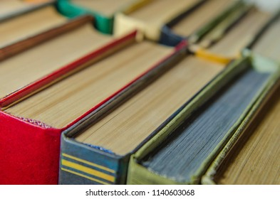 a stack of colorful books on the shelf in a library or a room close-up