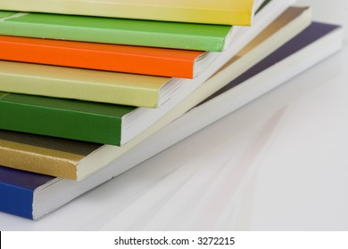 Stack of colorful books on white surface