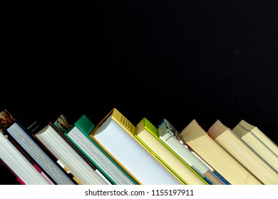 Stack of colorful books on wooden desk. Copy space for text. Back to school. Education background