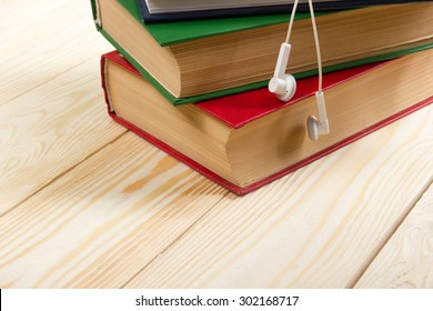 Stack of colorful books on wooden table and headphones. Audiobook concept