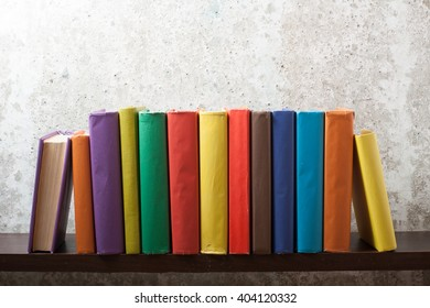 Stack of colorful books on wooden shelf at abstract backdrop. Education background. Back to school. Copy space for text.