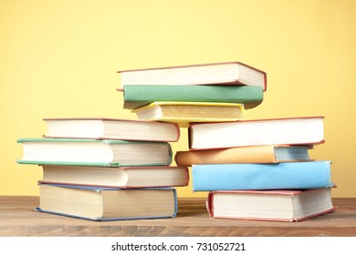 Stack of colorful books on wooden background. Back to school. Copy space for text. Education concept.