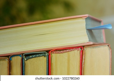 A stack of colorful books. One lies with a bookmark. Education, knowledge, learn, study and wisdom concept. Horizontal layout of childrens books. Front of books with colorful covers.