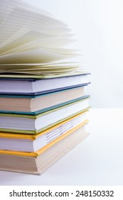 A stack of colorful books and open book. Ideas for business and self-development. Study background.