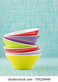 A stack of colorful bowls on a textile surface and background with copy space