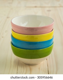 Stack of Colorful Bowls on Wooden Background