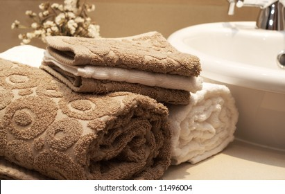 Stack of colorful brown and white towels on the table in the bathroom