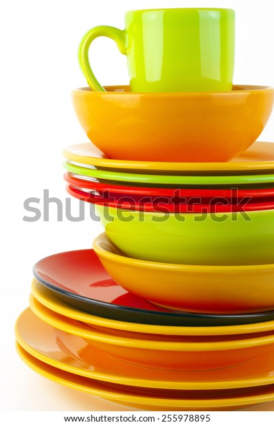 Stack of colorful ceramic dishware close-up on white background.