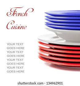 Stack of colorful ceramics plates on white background in blue, white and red, illustrating concept of french cuisine