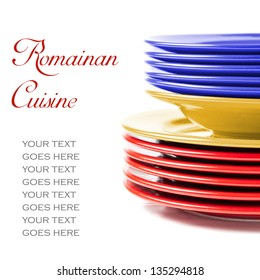 Stack of colorful ceramics plates on white background in yellow, blue and red, colors of Romanian flag, illustrating concept of Romanian cuisine