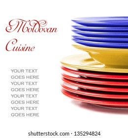 Stack of colorful ceramics plates on white background in yellow, blue and red, colors of Moldovan flag, illustrating concept of Moldovan cuisine