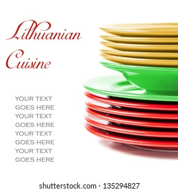Stack of colorful ceramics plates on white background in yellow, green and red, colors of Lithuanian flag, illustrating concept of Lithuanian cuisine