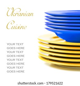 Stack of colorful ceramics plates on white background in blue and yellow, colors of Ukrainian flag, illustrating concept of Ukrainian food