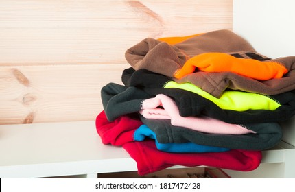 Stack of colorful fleece jackets laying on a white shelf in a wooden room interior