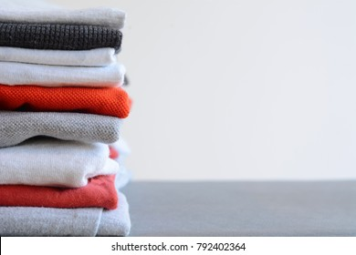 Stack of colorful folded shirts on gray table with empty space for text. Household concept.