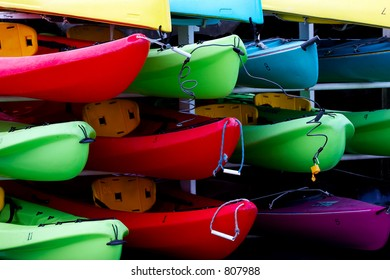 A stack of colorful kayaks waiting for active people to rent them.