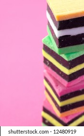 A stack of colorful liquorice allsorts on a pink background.